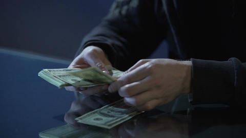 Hands of contract killer or bank robber counting money paid for committing crime Live Action