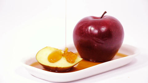 Pouring honey on red apple and red apple slice on white plate with honey isolate Footage
