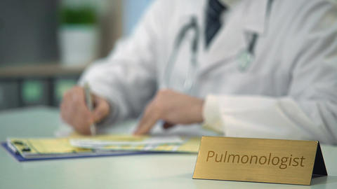 Pulmonologist prescribing medication to treat asthma, filling out medical forms Live Action