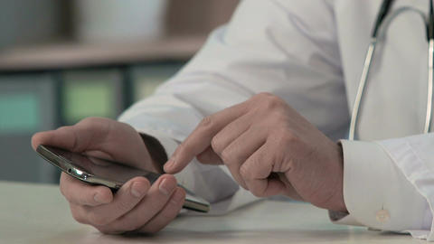 Physician's hands sliding files, typing text on smartphone, medical consulting Footage