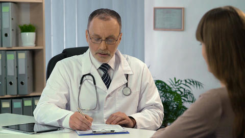 Woman talking to doctor, physician prescribing medication to patient in clinic Live Action
