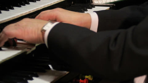 Organist playing 3 keyboards and pipe organ