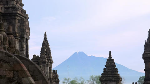 Prambanan Hindu temple complex against active volcano Mount Merapi. Indonesia Footage