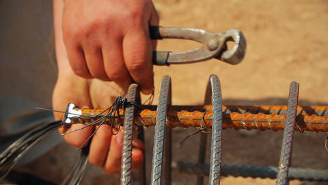 Worker preparing steel poles at construction site. He bundle wire on steel rod Live Action