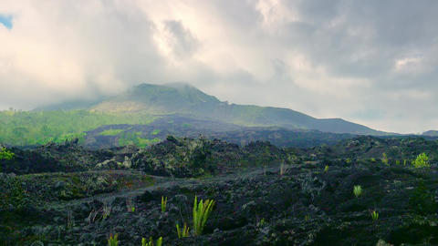 Smoking crater of erupting Mount Batur volcano and deserted land covered with la Footage