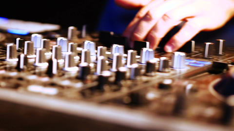 Hands of DJ tweak various track controls on DJ mixer console at nightclub Footage