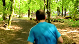 athlete runs through the forest - steadicam Footage