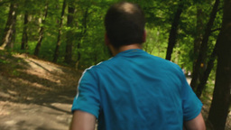 athlete runs through the forest - steadicam Footage