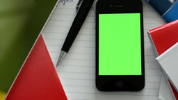Smartphone (green screen) with workbooks, paper and pen - closeup Footage