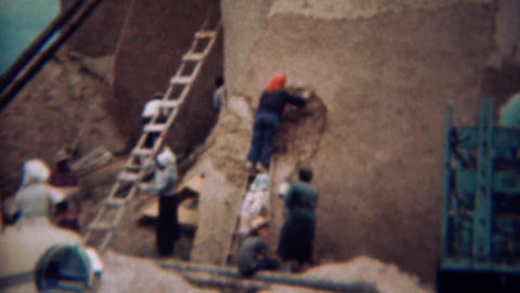 1959: Exterior adobe style building repair by women of the community Footage