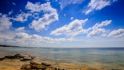 Clouds Motion above Stones in Transparent Shallow Sea Blue Sky Footage