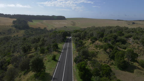 Aerial footage of 2 cars driving along country highway Footage