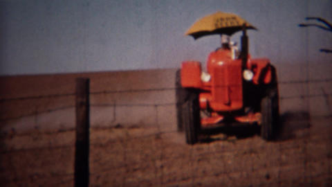 1951: John Deere umbrella tractor grading the fields Footage