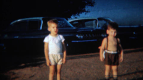 1959: Chickens roam free behind toddler boys in parking lot Footage