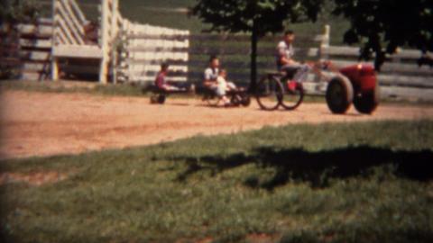 1951: Odd farm riding lawnmower pulling train of children in wagons Footage