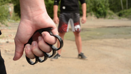man threatens man with knuckle-duster - outdoors Footage