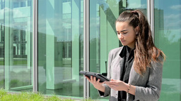 Business woman looks at tablet before business building Footage