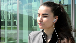 Bussines woman listens to music on headphones before bussines building Footage