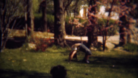 1948: Girl balances on head crab walks across yard Footage