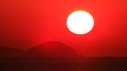 large red sun disk appears from behind cloud sea at foreground Footage