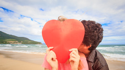 Girl behind Large Red Heart Guy Appears Kisses on Beach Footage