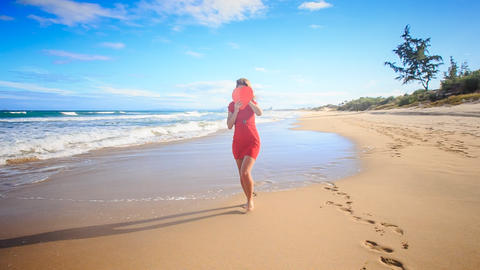 Blond Slim Girl Walks along Surf Hides Face with Red Heart Footage