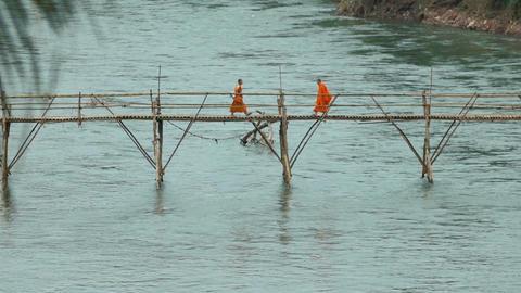 Monks walk bamboo bridge over river in Luang Prabang Acción en vivo
