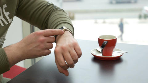 Teenager man checking for new email on smartwatch at a coffee shop Live Action