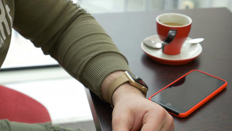 Young man using smartwatch email app while sitting at coffee shop Live Action
