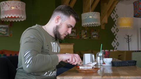 Man with smartwatch eating dessert cake pie in the restaurant Footage