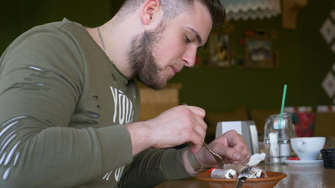 Closeup view of a young man with smartwatch eating delicious cake in a cafe Footage