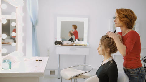 Female hairdresser of luxury beauty salon is standing and working with young blo Live Action