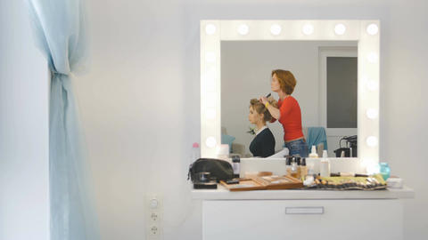 Reflection thru mirror - Female hairdresser of luxury beauty salon is standing a Footage