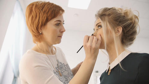 Professional make-up artist applying makeup on the face of the beautiful young s Live Action