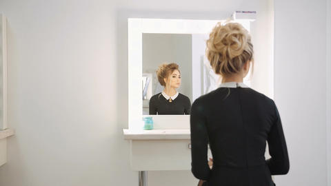 Beautiful blond model looking into the mirror in the beauty salon Footage
