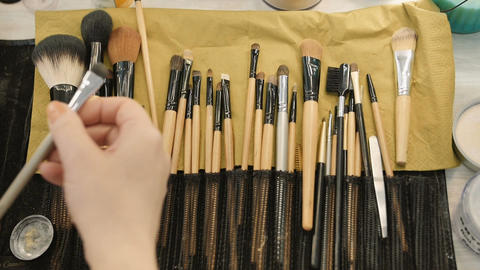 Make-up artist taking brushes from professional brush set. Beauty, makeup and fa Live Action