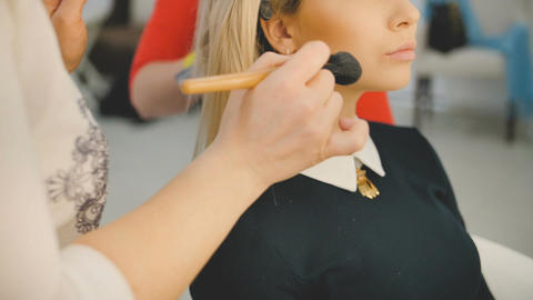 Close up shot of professional make-up artist applying makeup on the face of the Footage