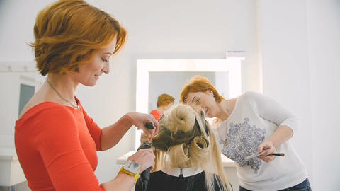 makeup artist and hairdresser preparing blonde model for the future shooting in Footage