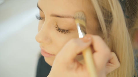 Close up shot of professional make-up artist applying makeup on the face of the  Live Action