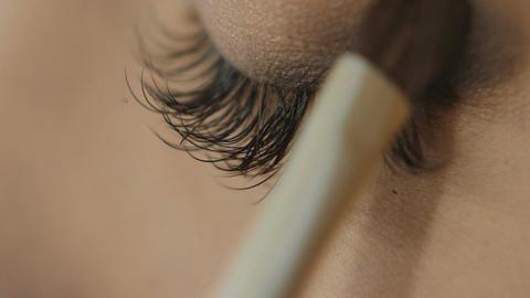 Professional Eye makeup artist applying eyeshadow powder. Beautiful woman face Footage