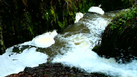Slow motion. Turning of foam on dirty water bellow rapids. Terrible smell muddy  Live Action