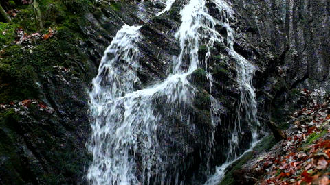 Slow motion. Small waterfall full of water after rain. Reflections on wet basalt Footage