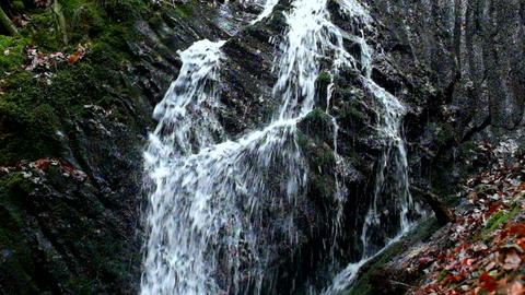 Small waterfall full of water after rain. Reflections on wet basalt boulders, mi Footage