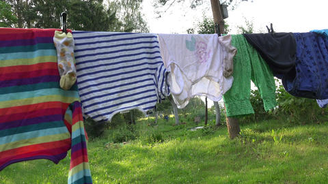 Family laundry in summer farm yard on string Footage