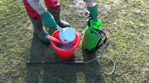 Gardener sprayer sprinkler in spring and chemicals Live Action