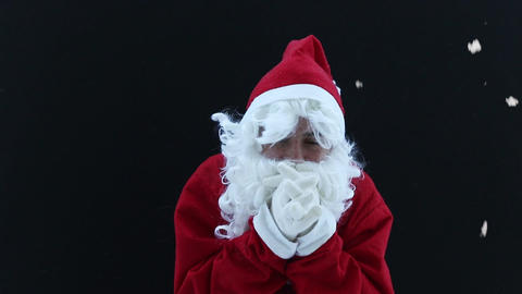 Santa Claus shivering and warm up with hands in front of black background Footage