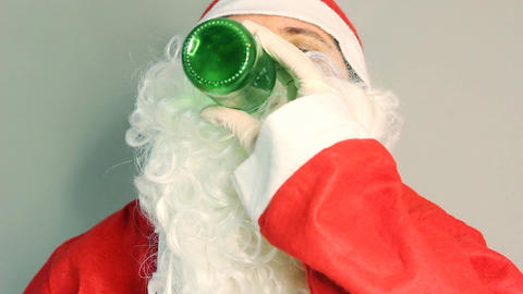 Drunken santa claus drinking beer in front of grey background Footage
