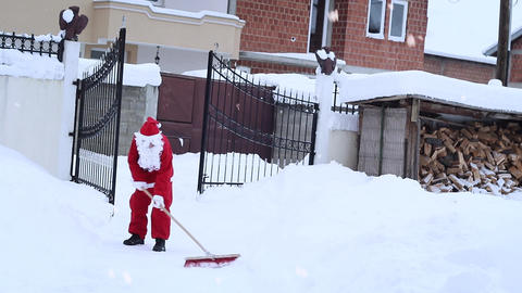 santa claus sweep snow from road in winter, cleaning road from snow storm Footage