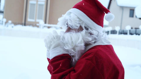 Santa Claus shivering and warm up sideways in front of snowy landscape