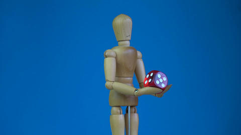 Wooden artist drawing manikin holding red game lucky dice and rotating Live Action
